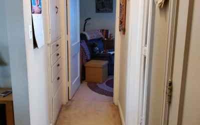 Hallway between bedrooms with built in storage and closet