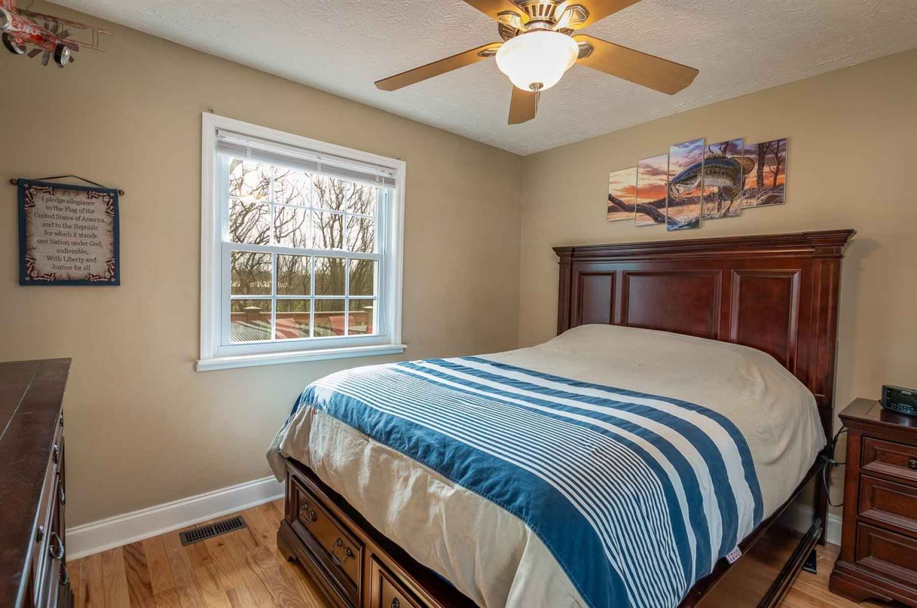 Second guest bedroom on main level.  Offers hardwood flooring, ceiling fan and neutral paint