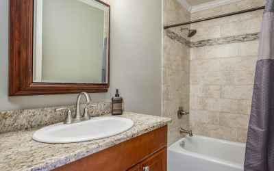 The full guest bath has surround tile shower, granite top vanity, ceramic tiled flooring and updated lighting