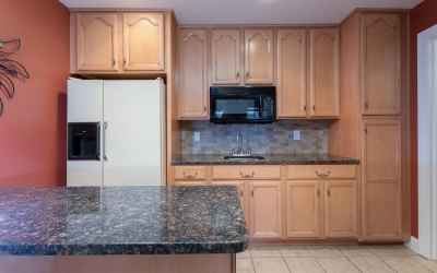 This large, efficiency kitchen has loads of cabinets, pretty back splash and granite countertops
