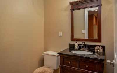 Full guest bath located in the basement has granite topped vanity, ceramic tiled flooring and updated lighting