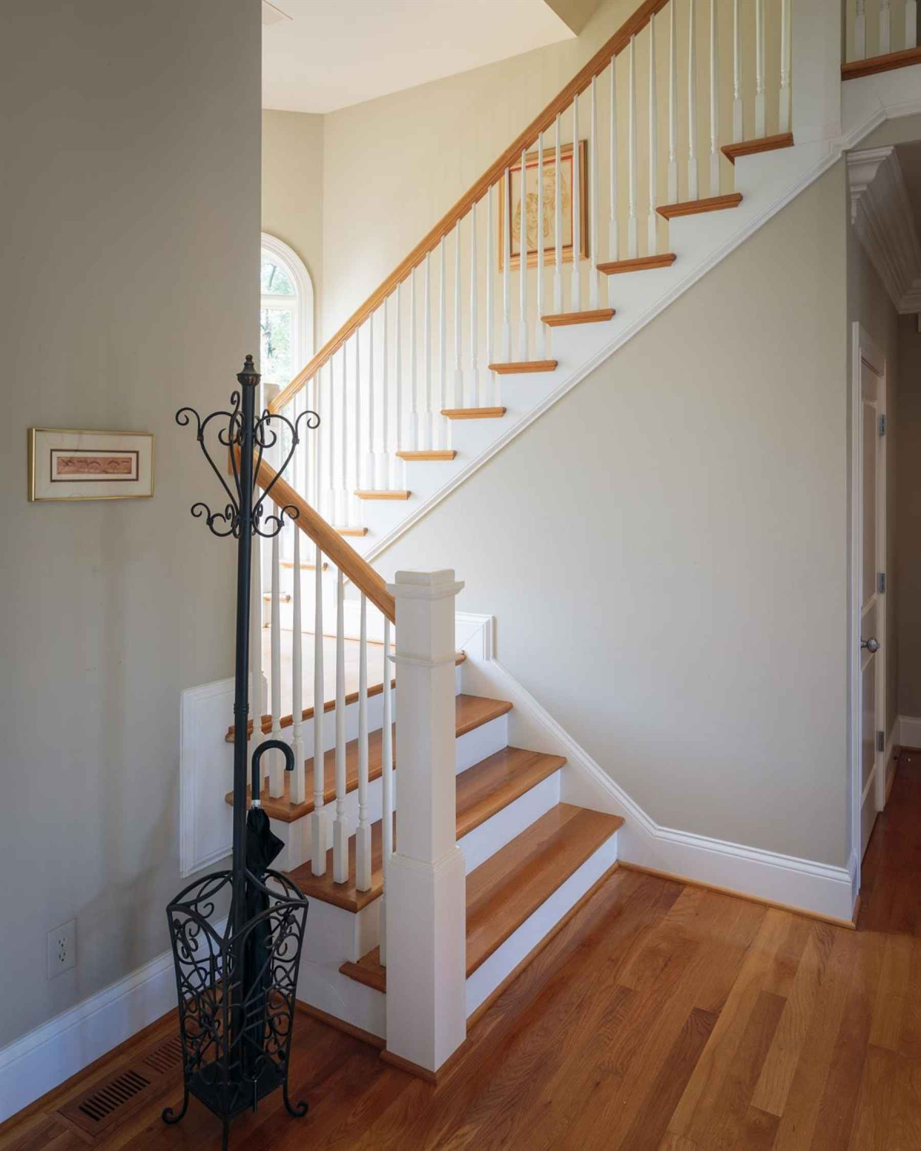 Stairwell to second floor flanked with large window allowing natural light to fill the space.