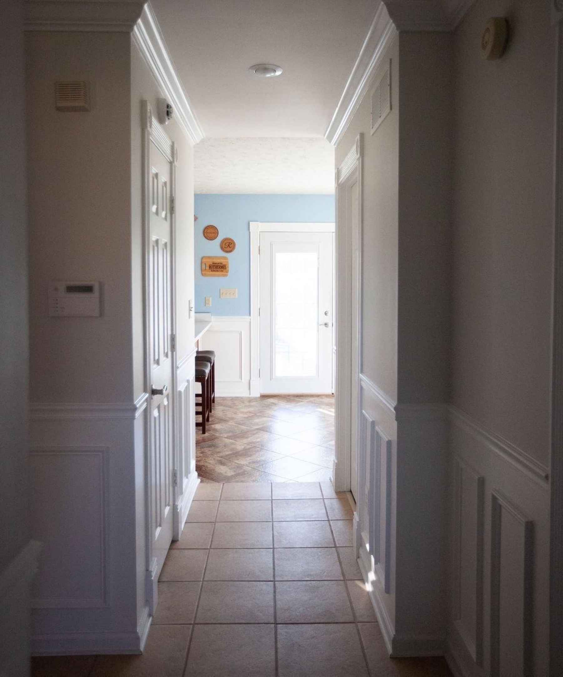Freshly painted hallway lined with crown molding and wainscoting leading to the kitchen.