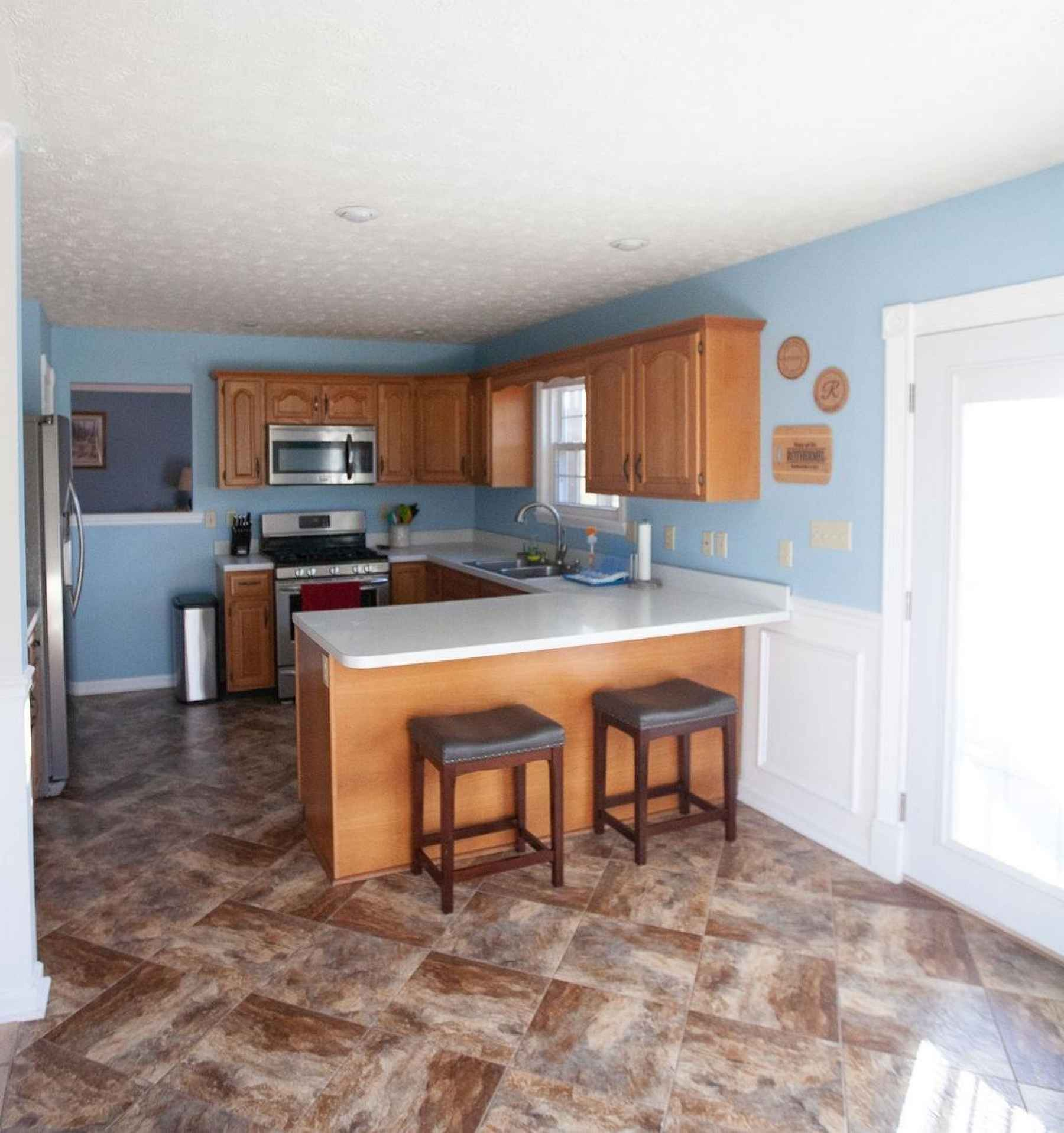 A spacious eat-in kitchen with a beautiful tiled floor, bar and oak cabinets