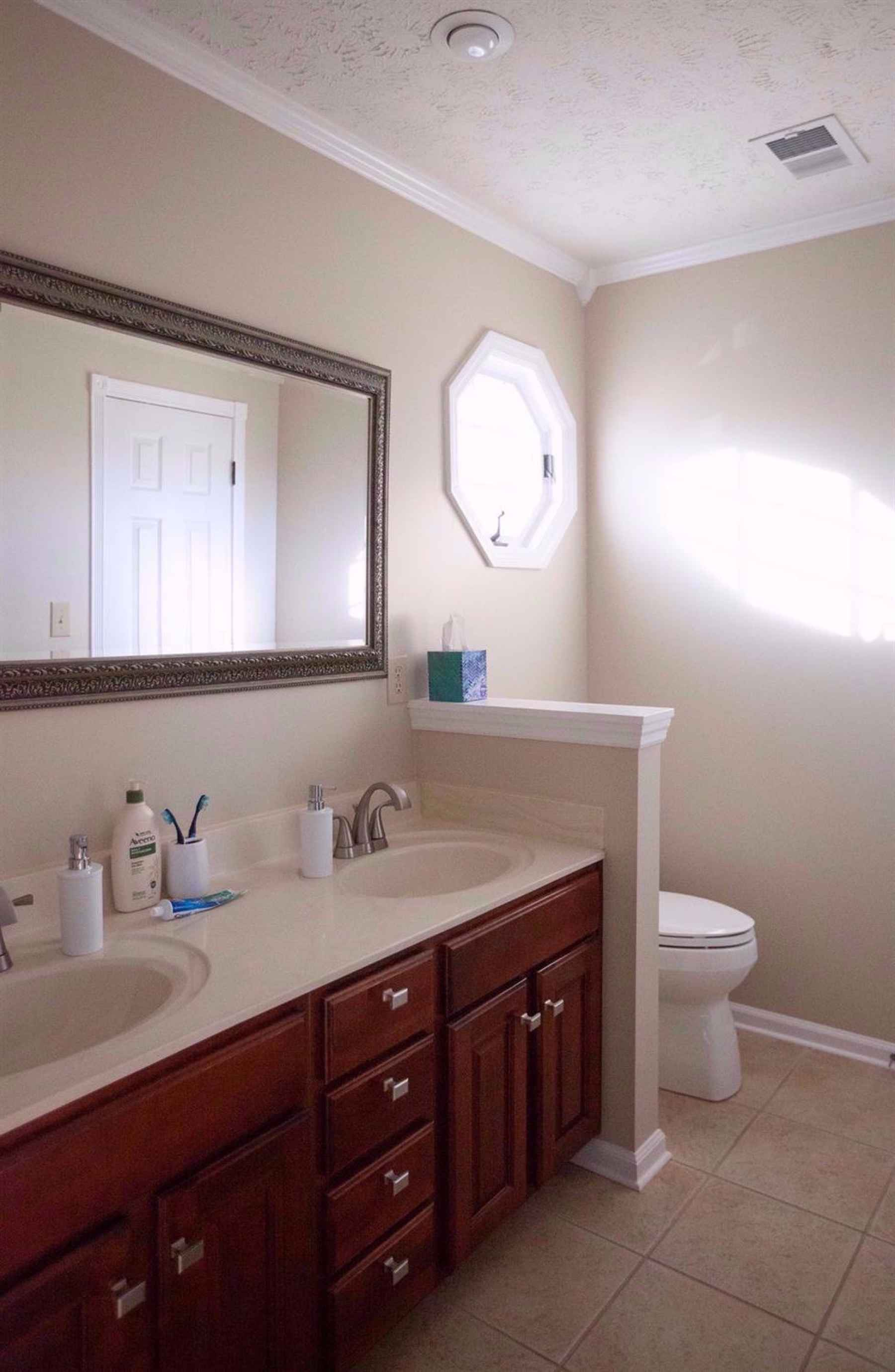 Master Bath with a tiled floor, double sink and retractable octagonal window.