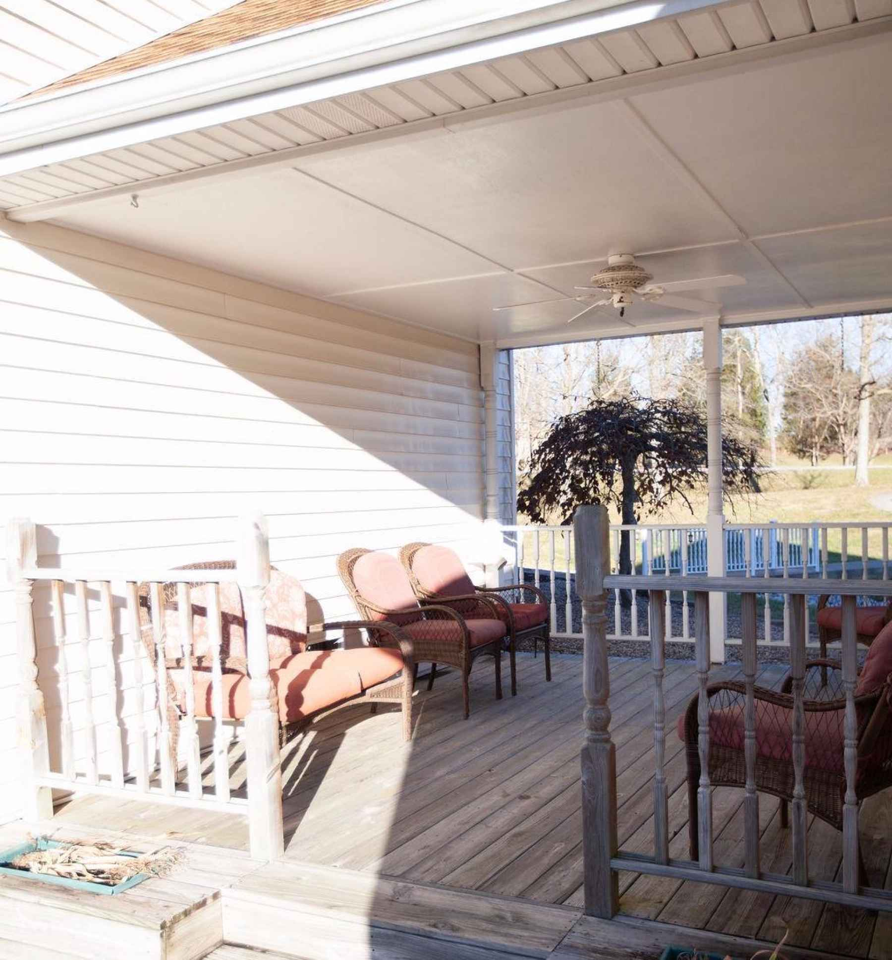 This breezeway connecting the home to the garage has a wonderful sitting area with a ceiling fan. Just another unique feature adding to the charm of this beautiful country home!