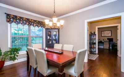 The formal dining room has hardwood flooring, crown molding, & plantation blinds.