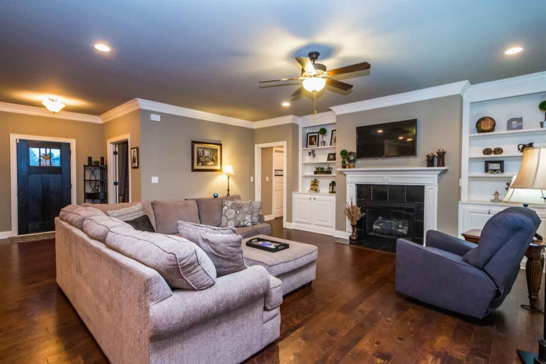 The great room features a gas-log fireplace, built-in bookcases, a ceiling fan, & crown molding.