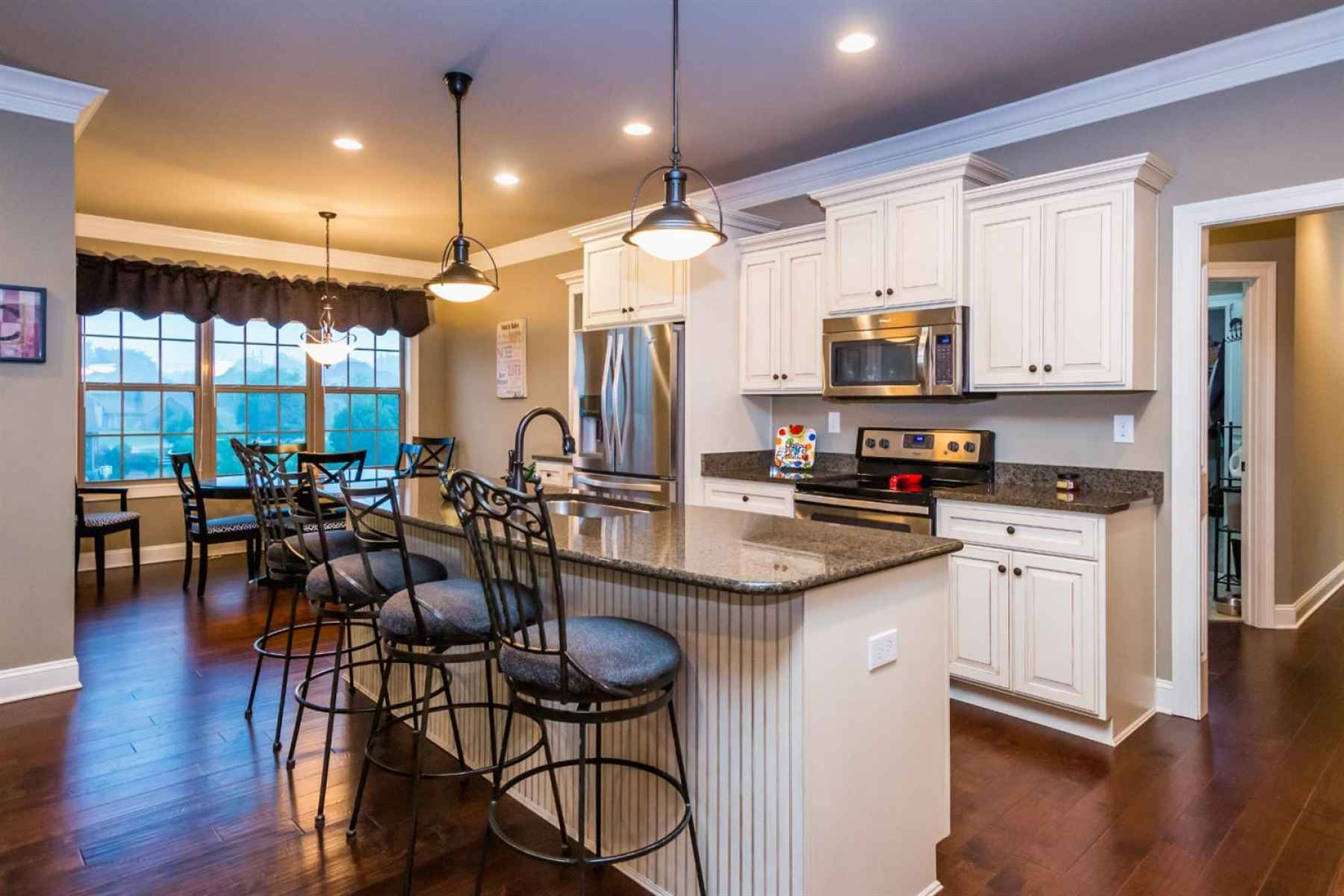 The kitchen has a huge island, granite counters, beautiful cabinets, a side-by-side refrigerator, dishwasher, smooth-top range, microwave, & a walk-in pantry!