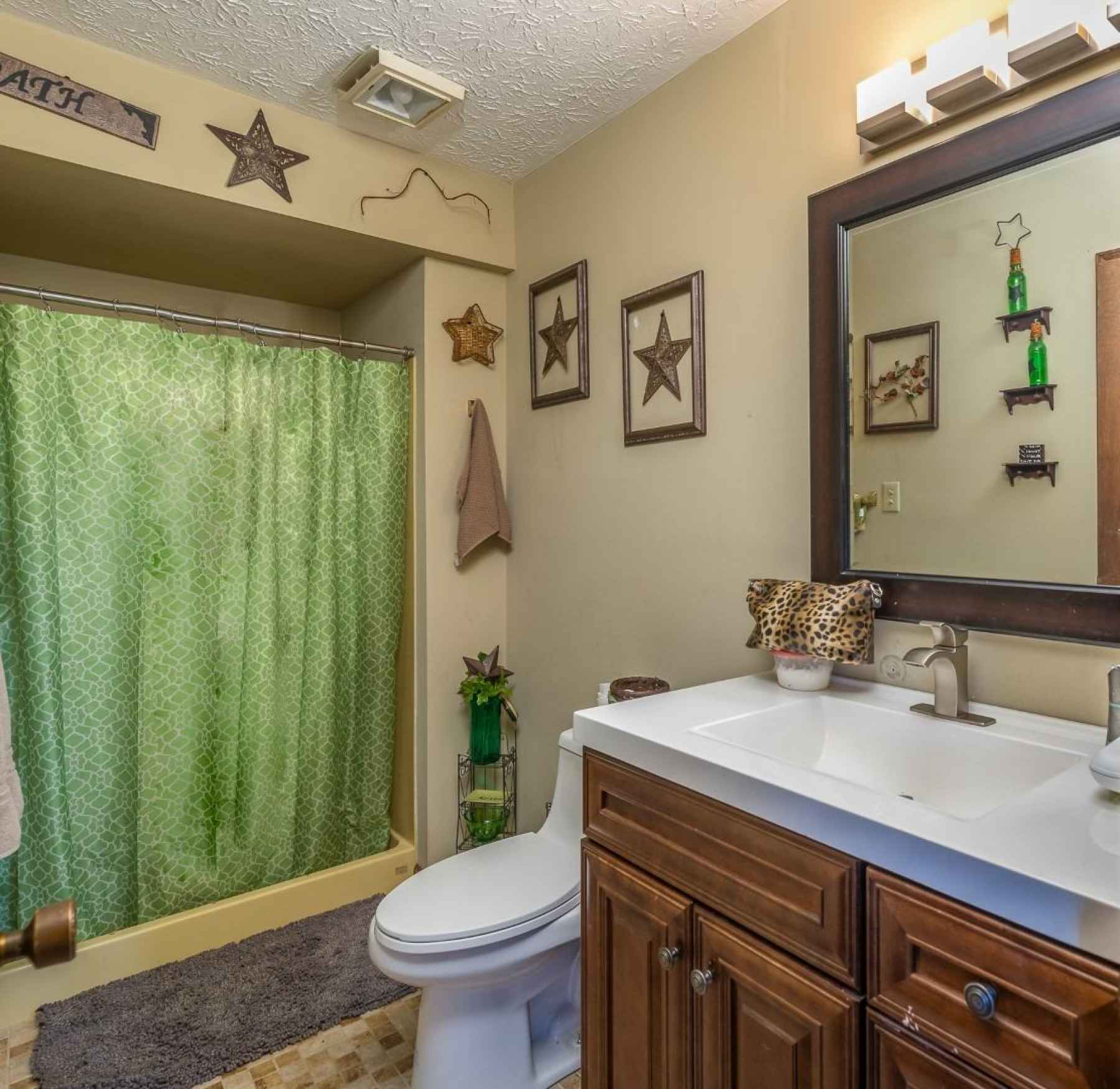 The second floor full bath has updated vanity, lights and fixtures as well as commode