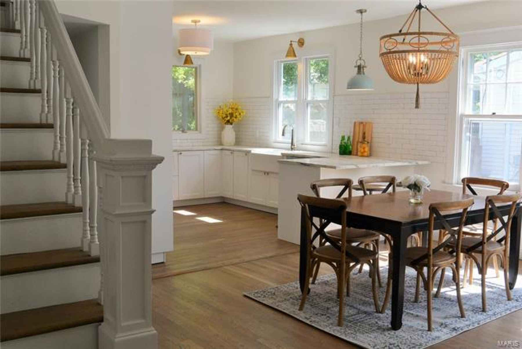 Dining area and new white kitchen. New dining light fixture, hardwoods throughout.