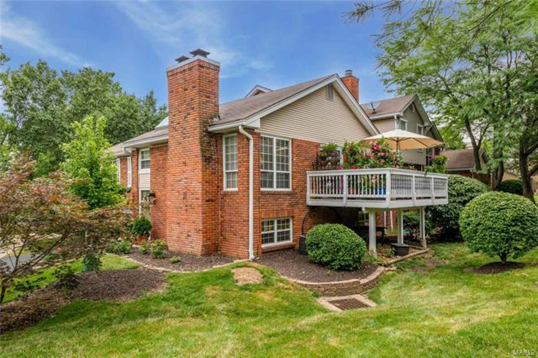 A view from the side shows off the beautiful landscaping and gorgeous deck
