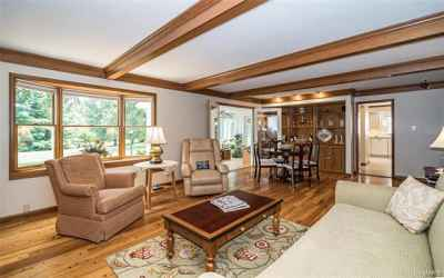 Large Family room with gas fireplace, hardwood floors, bay window and built-in bookcases on two sides.  Entry to sun room and wet bar as well.