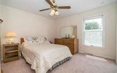 Bedroom with ceiling fan & built-in closet organizer.