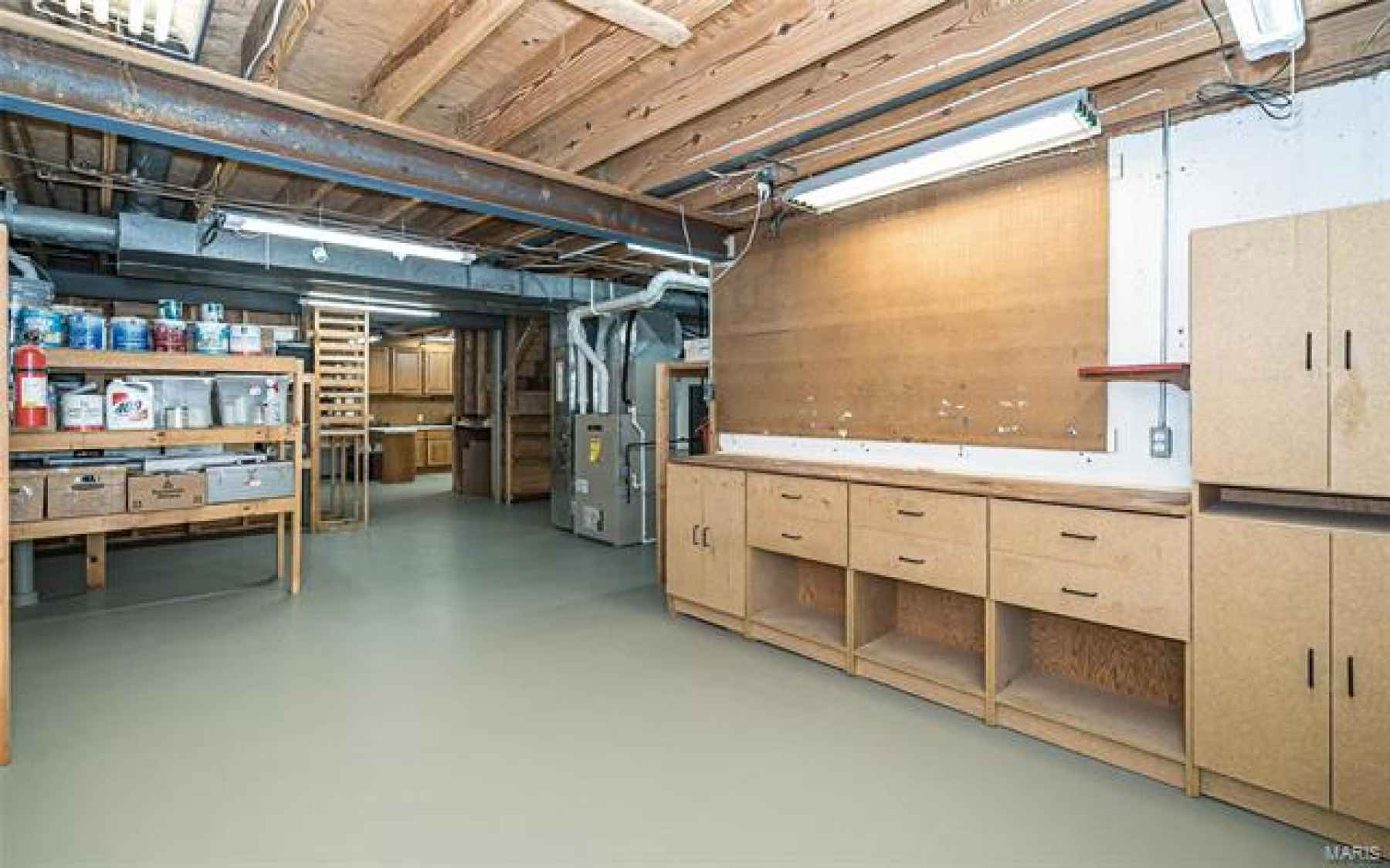 Newly painted walls & floor in unfinished Basement with purposely placed storage and cabinetry.