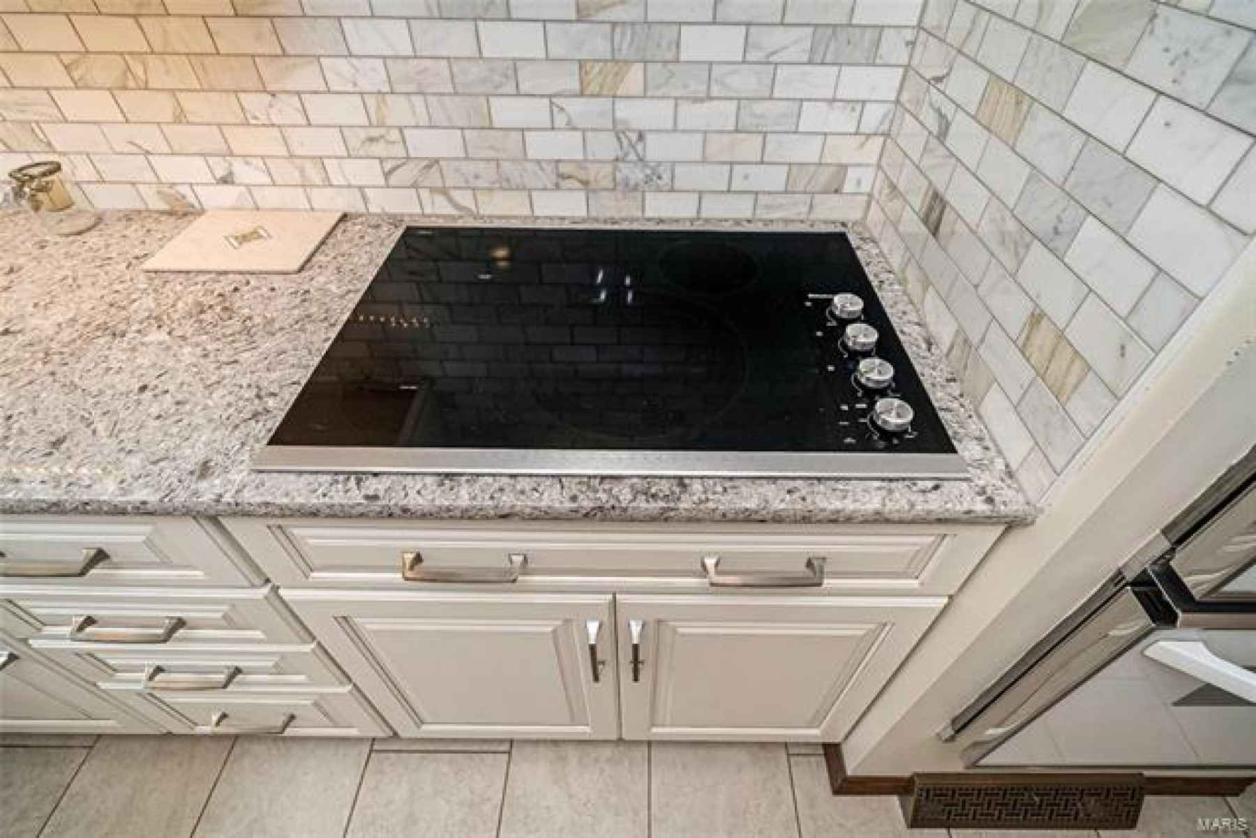 Newer even heat cooktop with retractable vent. Gorgeous marble back-splash and Quartz countertop.