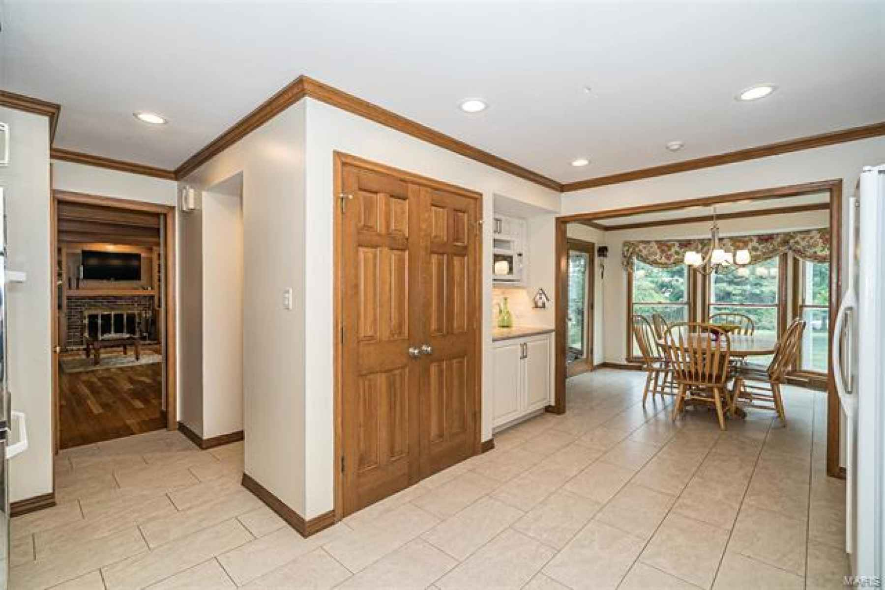 Designer Kitchen with view of yard from Breakfast room and family room. Notice the beautiful porcelain tile.