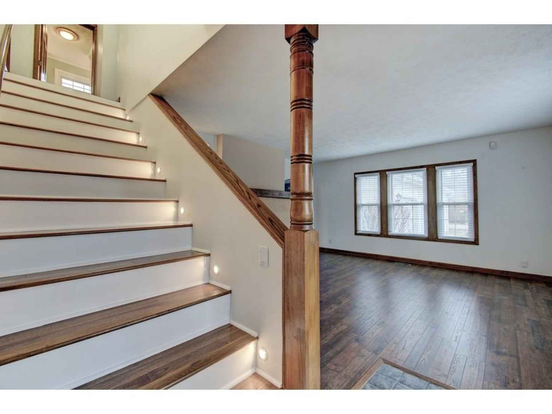 Entryway with extra wide staircase. All new flooring up and down.