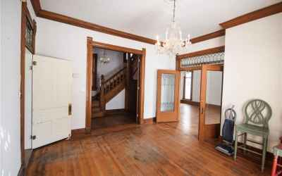 Main floor. Dining Room looking into the Great Room. Left doorway leads to stairs. French doors on t