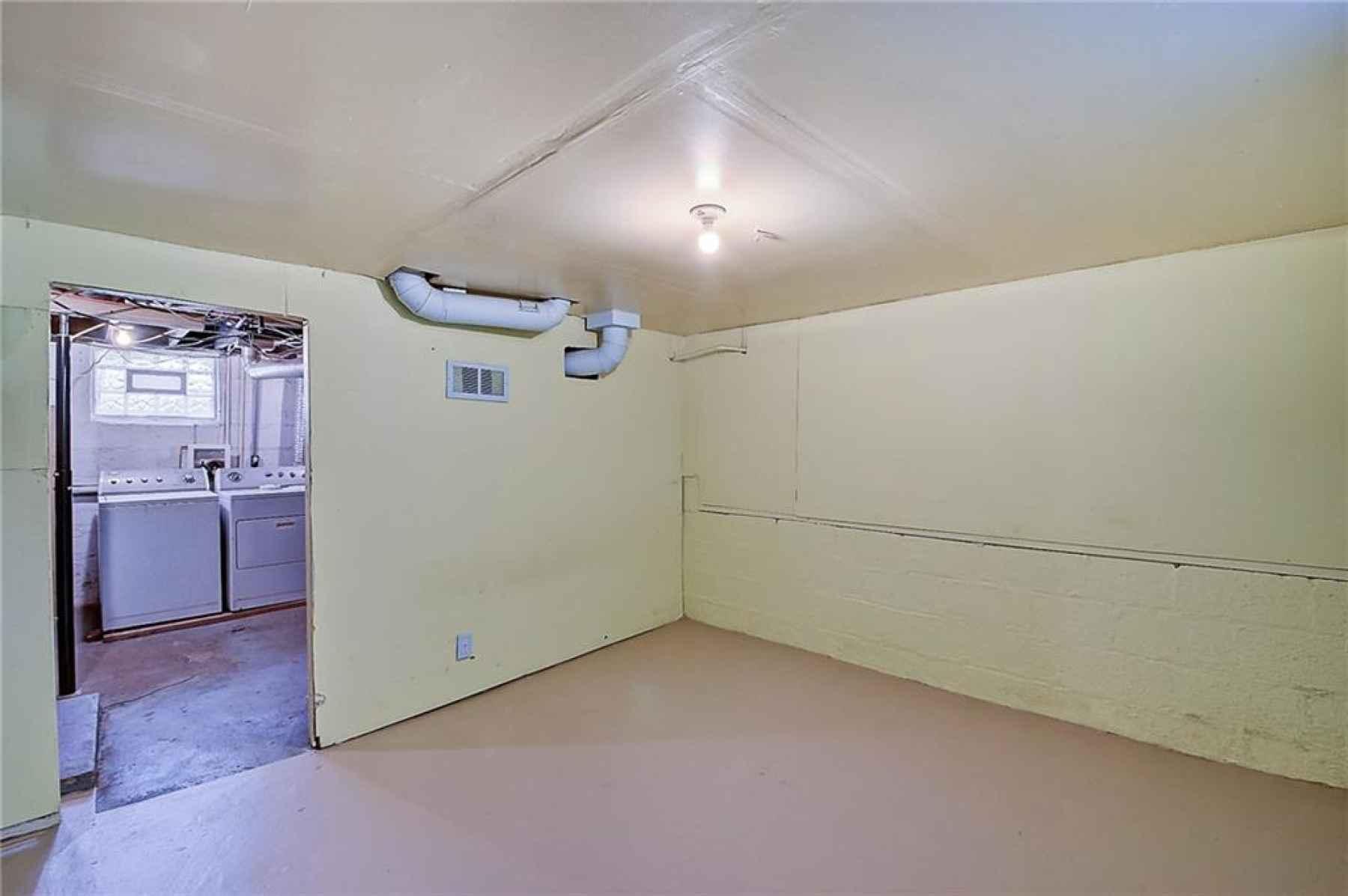 Basement bonus room looking into laundry and storage area.