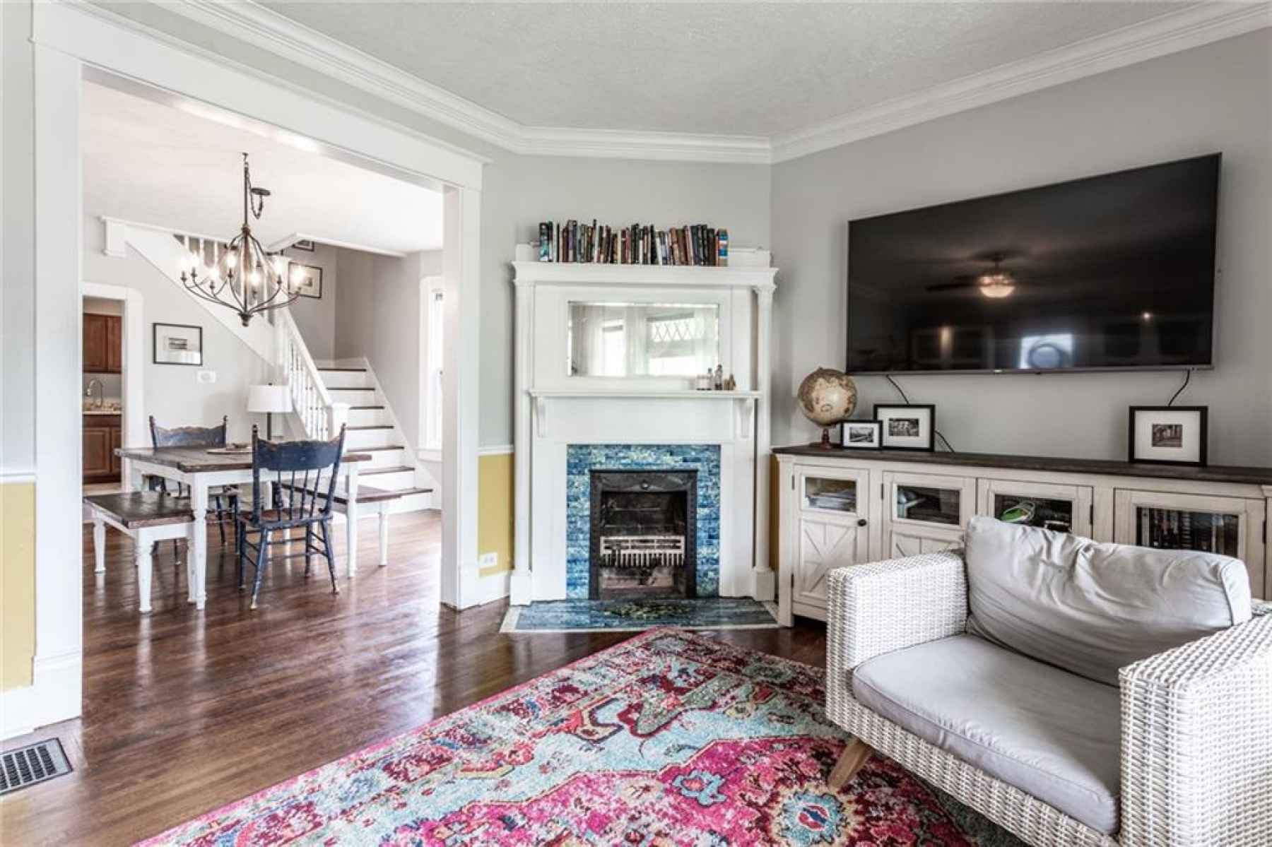 Original hardwood floors have been preserved beautifully and the custom, tile mantle adds charming p