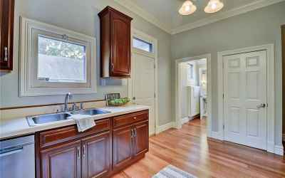Kitchen. Exterior door goes to back deck and yard. Hallway leads to pantry/mud room and half bath. D