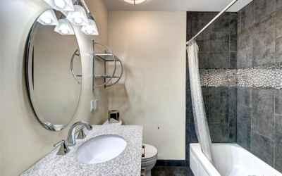 main floor hall bath has new sink, toilet, fixtures, tile in shower and flooring